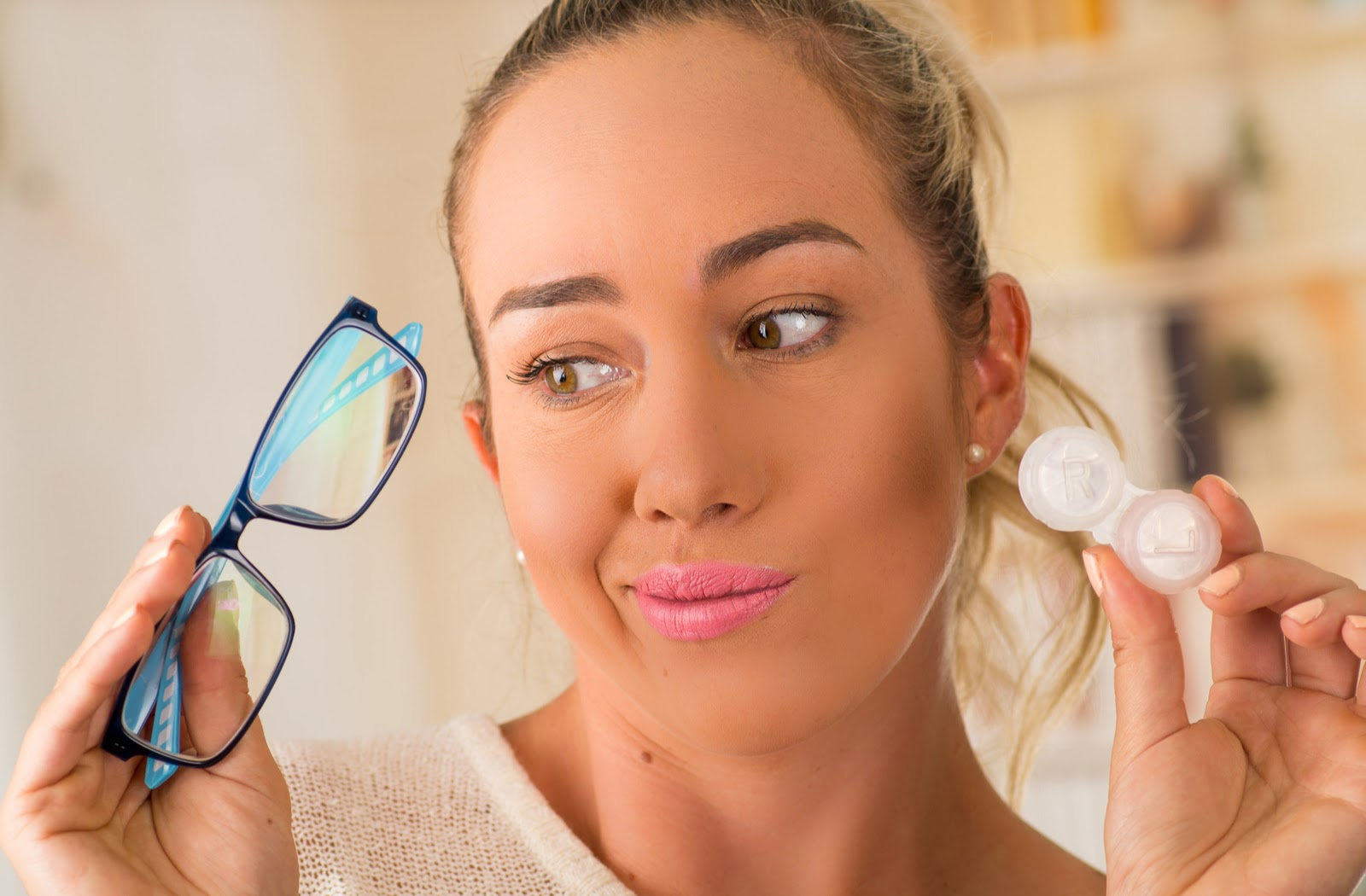 Young woman holding glasses in right hand and contact lens in her left hand wondering about which to pick for myopia control