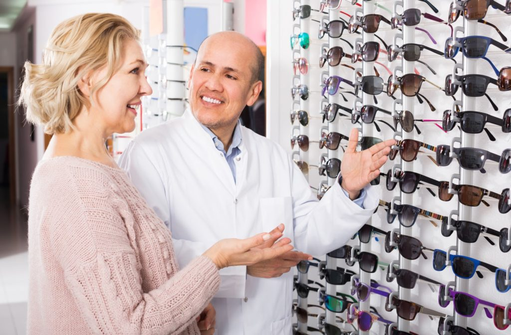 Optometrist showing patient available sunglasses she can get with prescription.