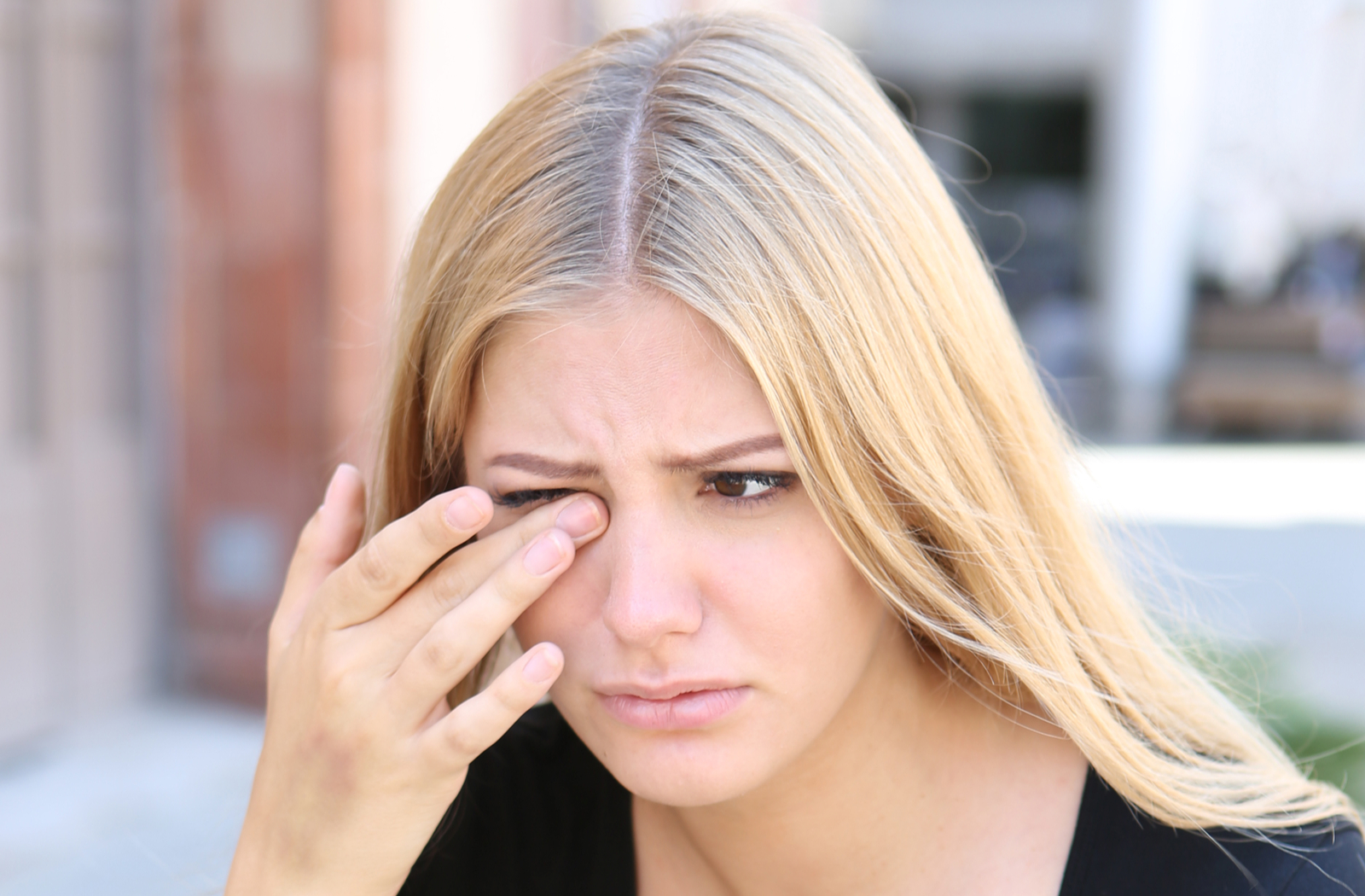 Young woman touching her right eye as she experiences discomfort