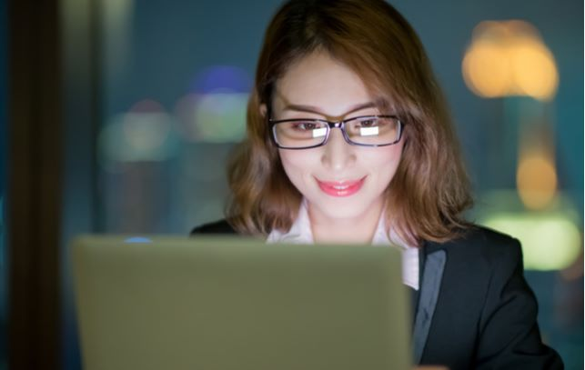 Business women wearing blue light glasses while she uses her laptop with blurred background