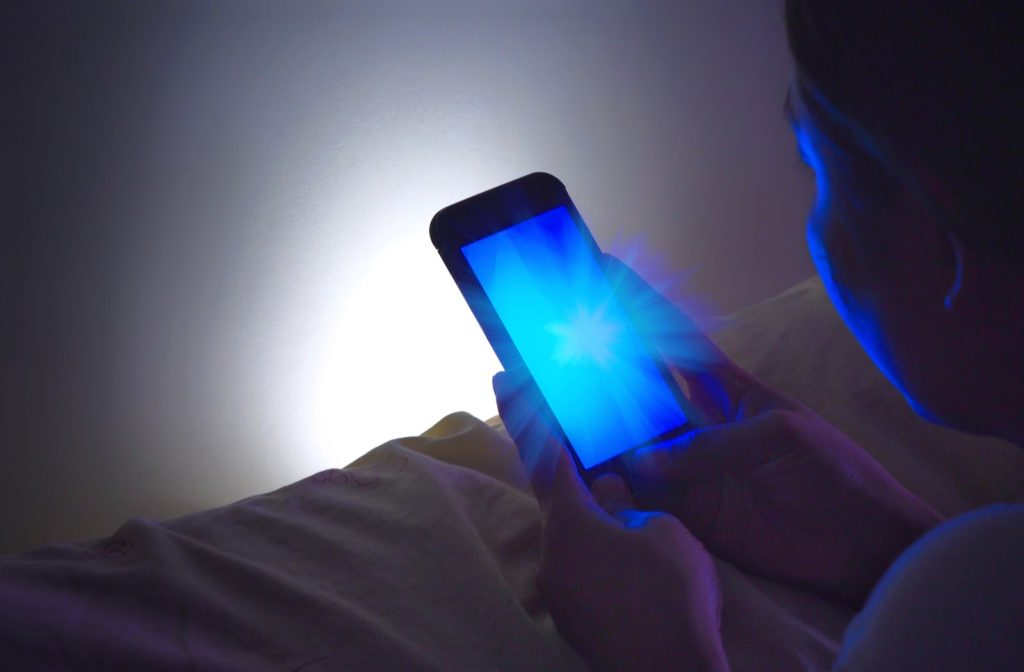 Light coming off smart phone as girl uses it at night